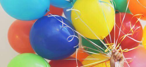 różnokolorowe balony trzymane w dłoni