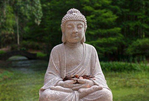 kamienna figura Buddy trzymającego monety
