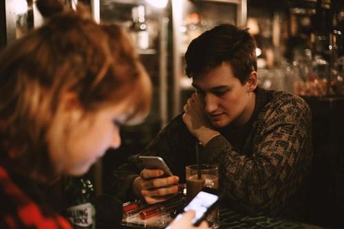 telefonlarıyla ilgilenen iki yalnız insan