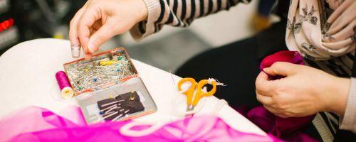 krawcowa trzymająca materiałw  kolorze madżenty