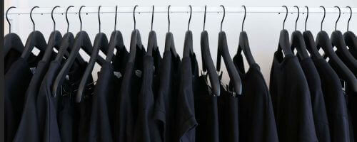 czarne garnitury ciasno zawieszone na wieszakach