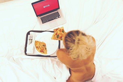 kobieta je pizze siedząc przed komputerem