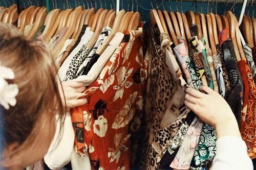 askıdaki elbiseleri inceleyen kişi