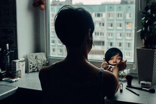 ayna karşısında makyaj yapan kadın