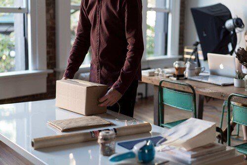 osoba pakująca towar w kartonowe pudełko