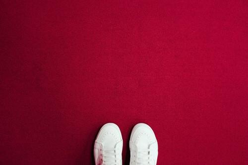 kırmızı fonda minimalist beyaz ayakkabılar
